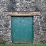 old green coloured door and stone wall