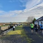 Three happy runners outside lock keepers cottage